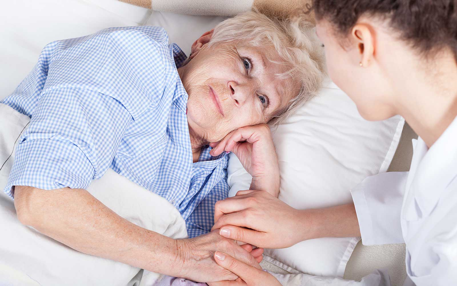 un'infermiera che tiene la mano di una signora anziana sdraiata