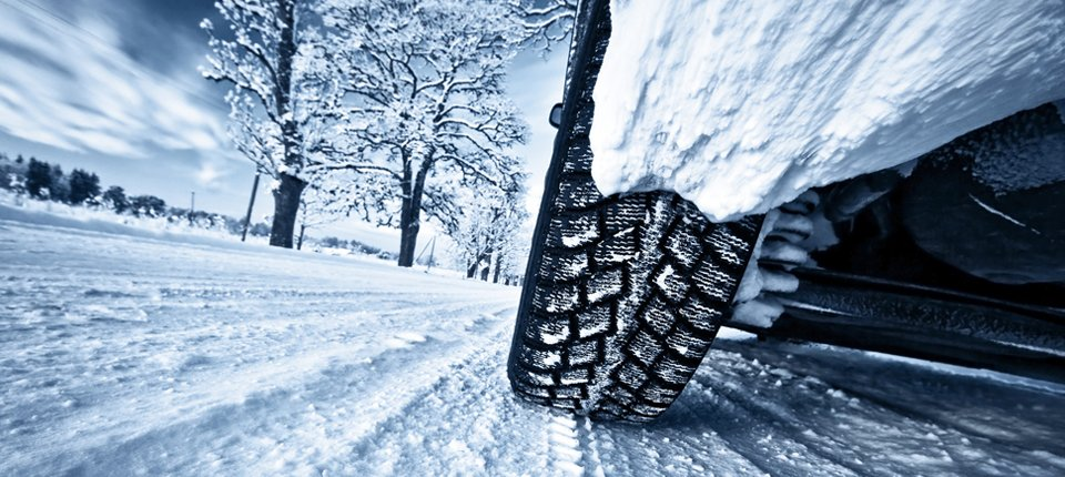 View from the ground of a car tyre on a snowy road