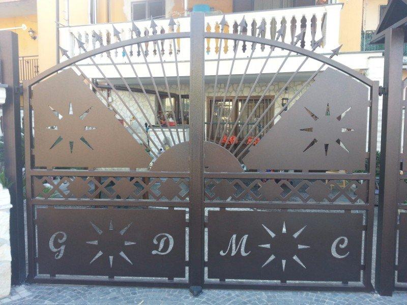 un cancello in ferro con dei soli disegnati e delle lettere