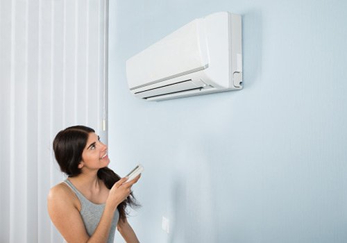 woman using remote air conditioner