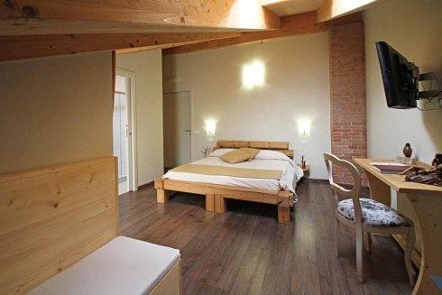una camera con un letto matrimoniale, una scrivania e una panca
