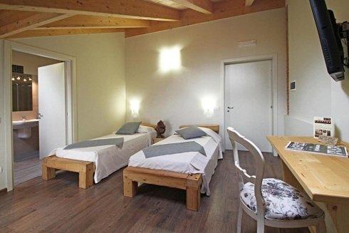 una camera con due letti singoli e una scrivania