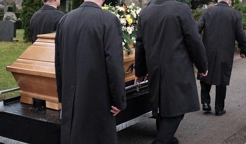 Portando il feretro al carro funebre,legno chiaro,rose bianche