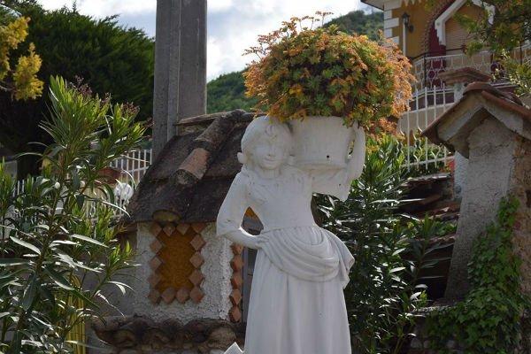 una statua di una donna che tiene un vaso di fiori