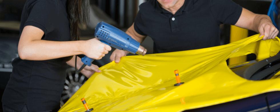 due uomini che riparano auto con telo giallo