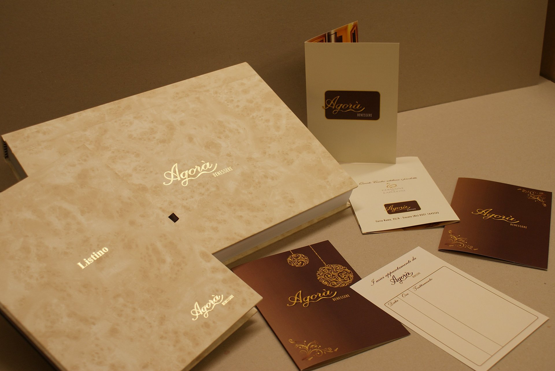 bigliettini da visita e copertine in beige con scritte in oro