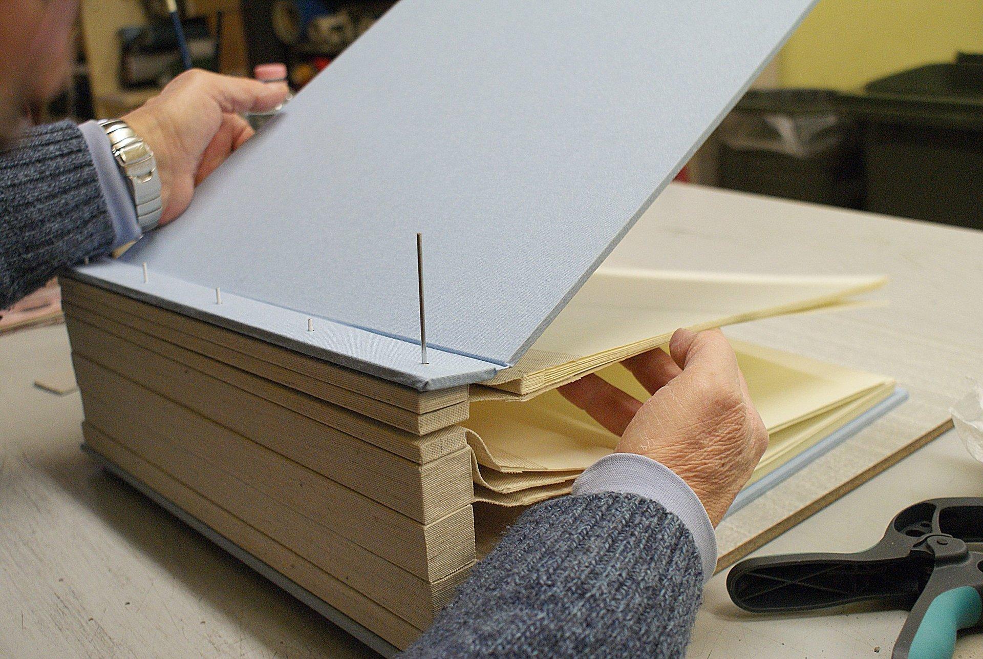 artigiano che aggiusta la rilegatura di un libro voluminoso