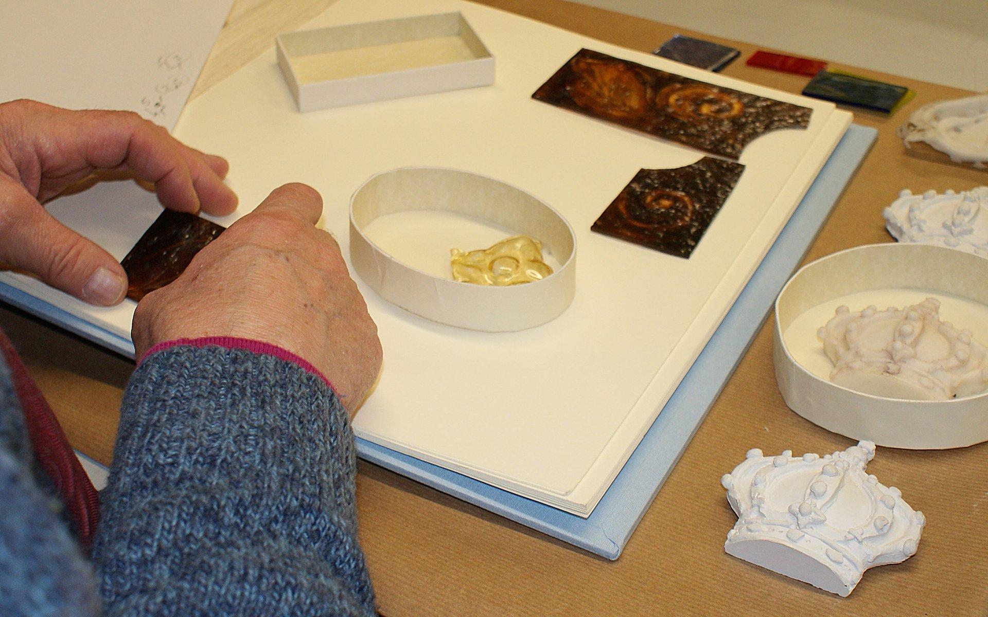 due mani che lavorano alla rilegatura e decorazione di un libro