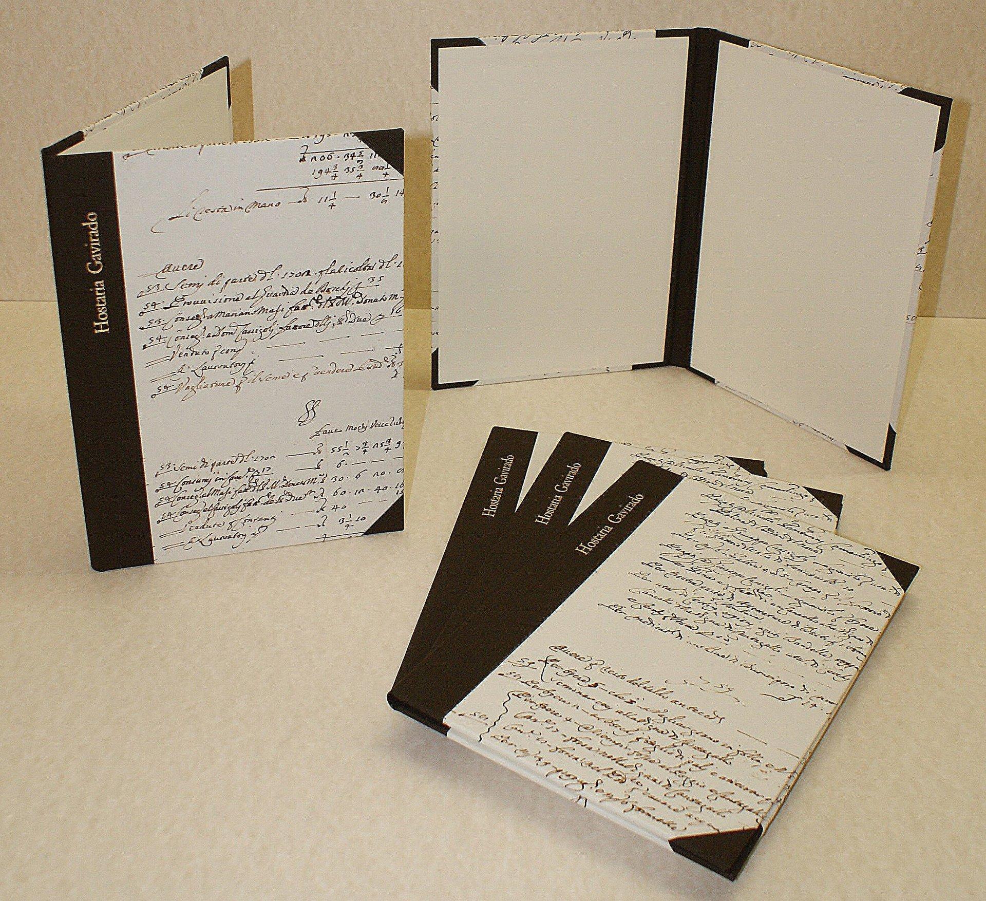 libri con pertina bianca e scritte color legno appena rilegato