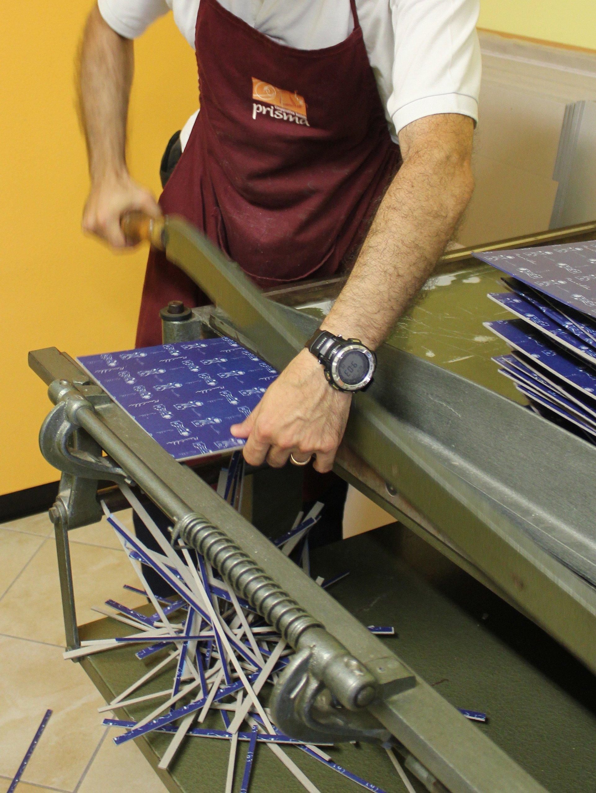 artigiano che lavora con un macchinario per rilegare i libri