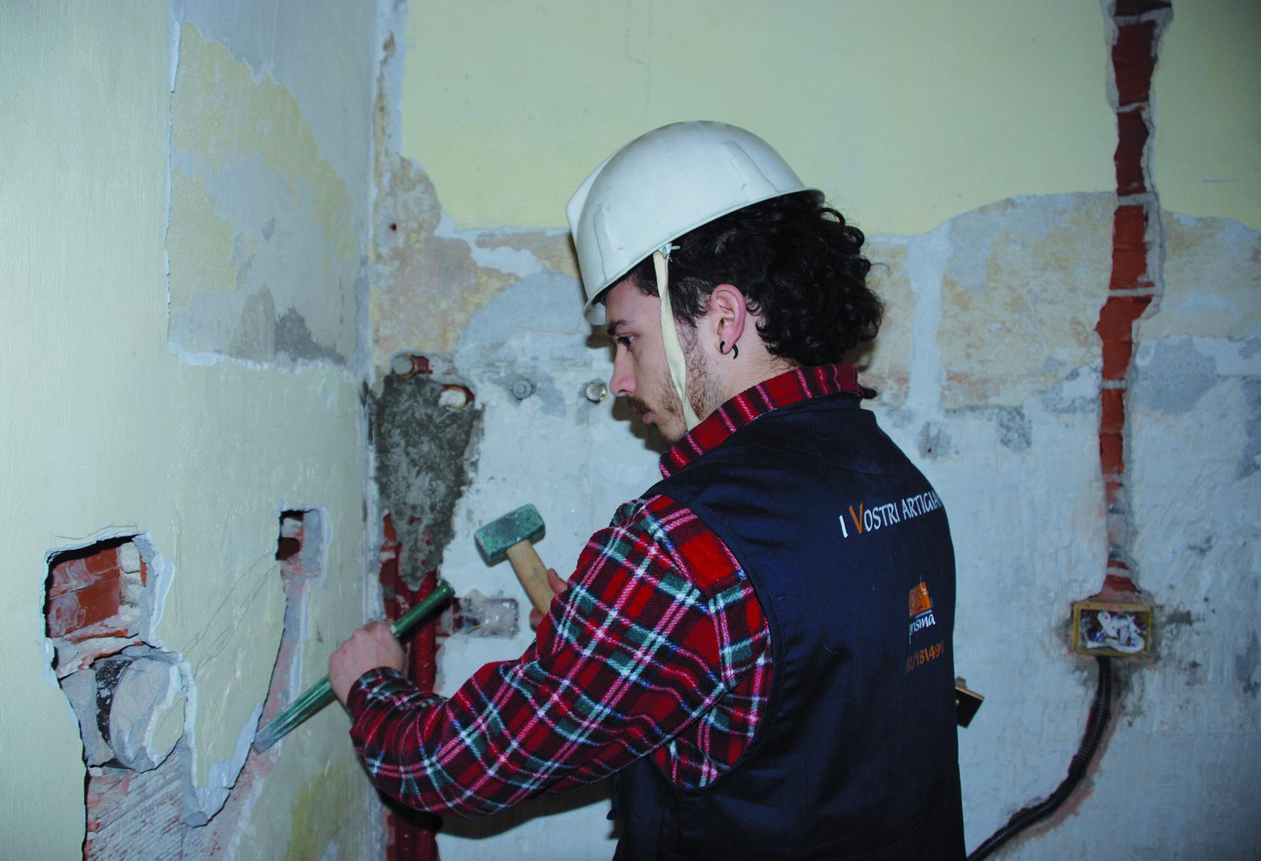 ragazzo con martello e scalpello che lavora su di una parete