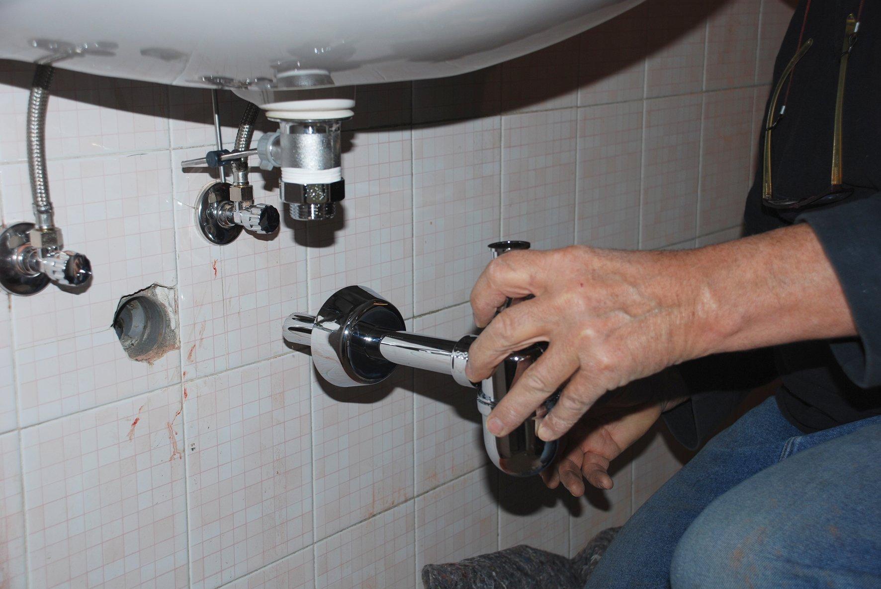 una mano che smonta il tupo di un lavandino
