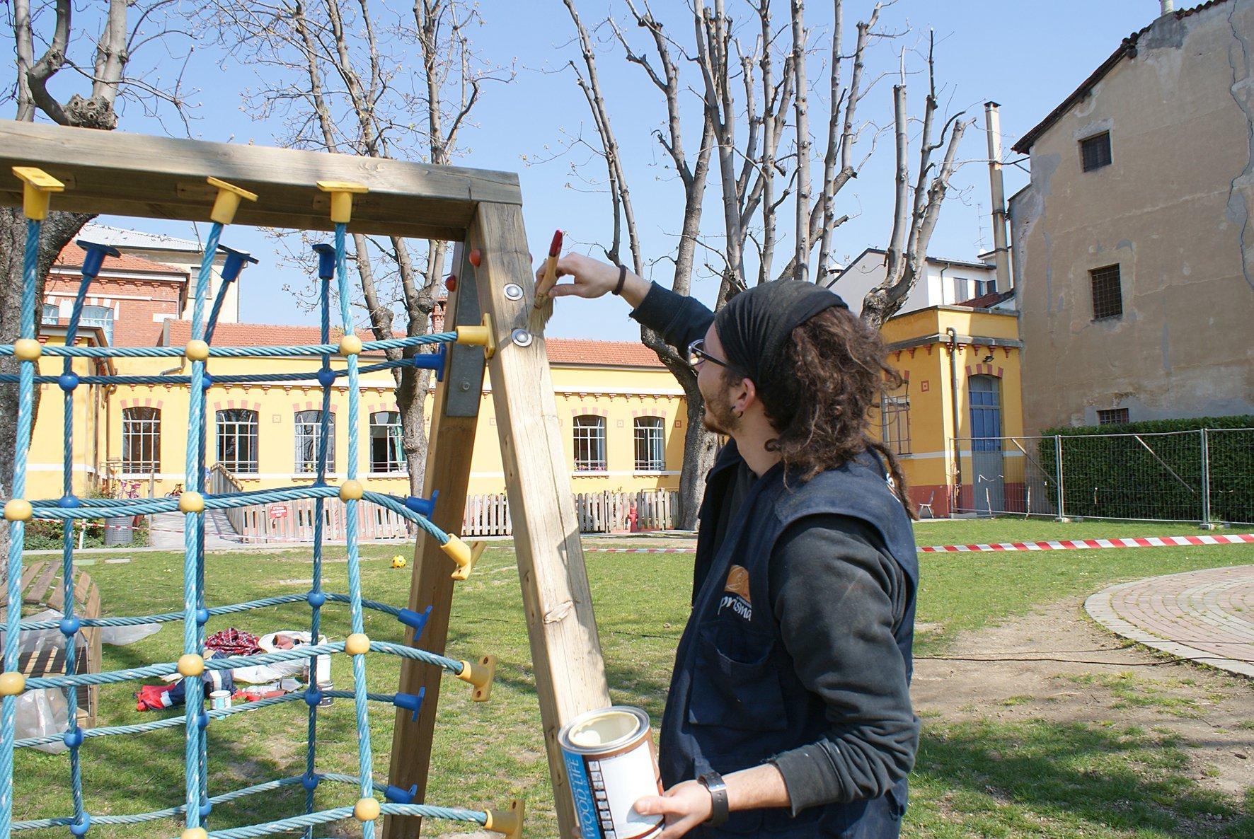 ragazzo che dipince una struttura per giochi da esterno