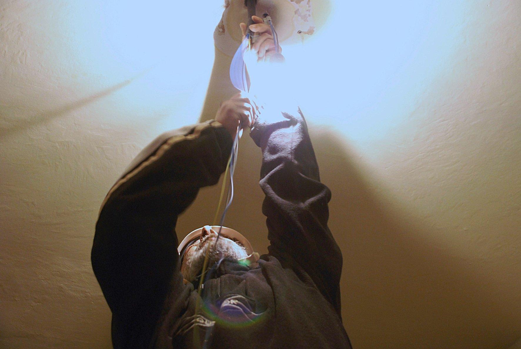 manovale che aggiusta una lampadina
