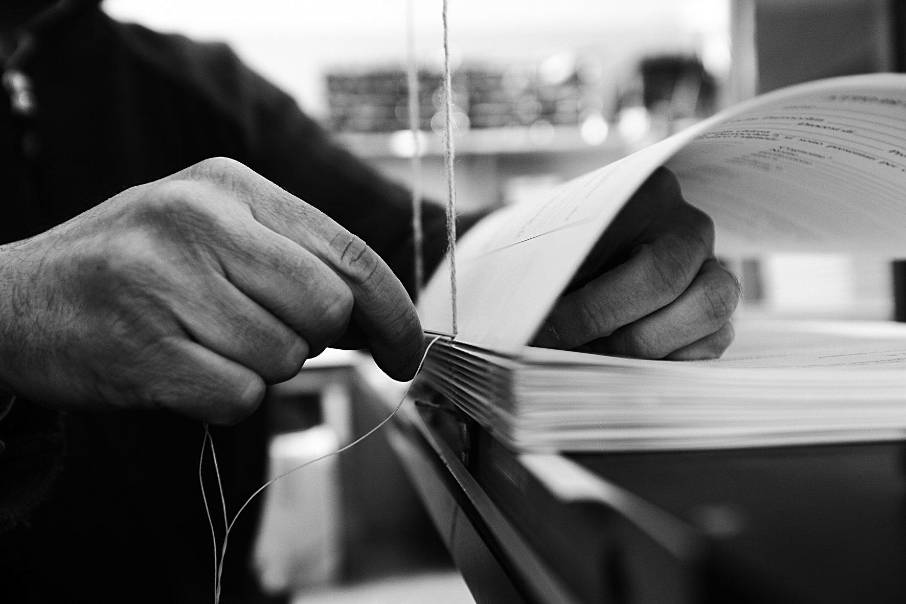 due mani mentre rilegano un libro