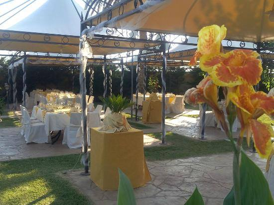 dei fiori arancioni e dei tavoli apparecchiati per una cerimonia all'esterno