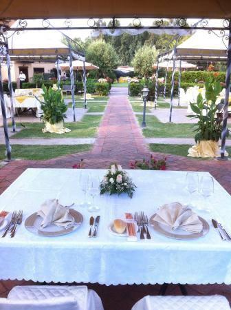 un tavolo apparecchiato per due con dei fiori e vista di altri tavoli in un giardino
