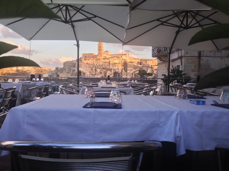 dei tavoli apparecchiati sotto a  degli ombrelloni
