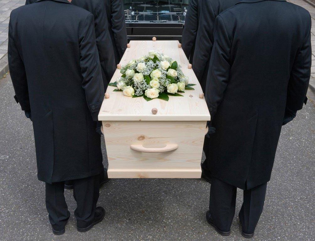 Bara bianca sorretta da uomini vestiti a lutto