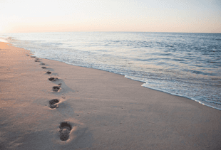 Footsteps on a beach with sunset in the background