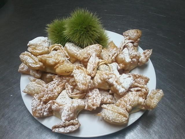 un piatto con dei dolci fritti con zucchero a velo