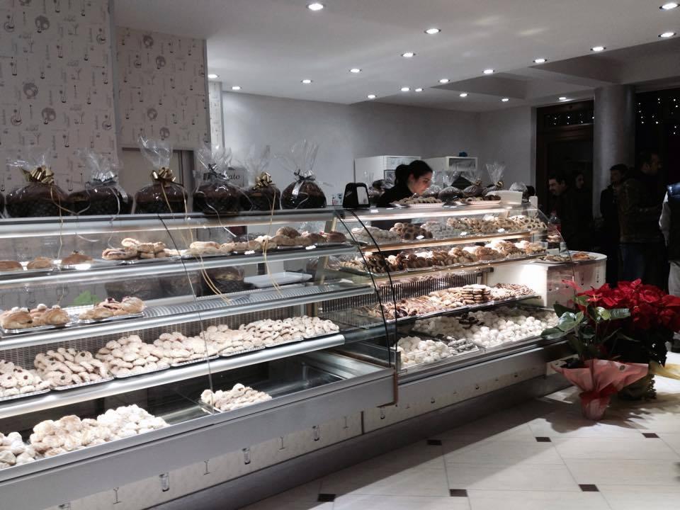 Una vetrina con dei pasticcini ,dolci e panettoni sopra a un banco
