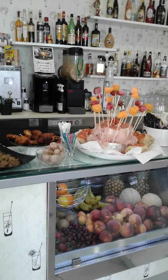 Una vetrina con della frutta, un bancone con degli stuzzichini, degli antipasti, una macchina del caffè e delle mensole con dei liquori dietro al bancone