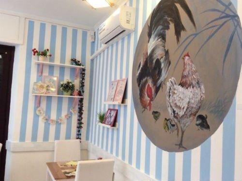 una parete bianca e azzurra  con un disegno di due galline. interno ristorante