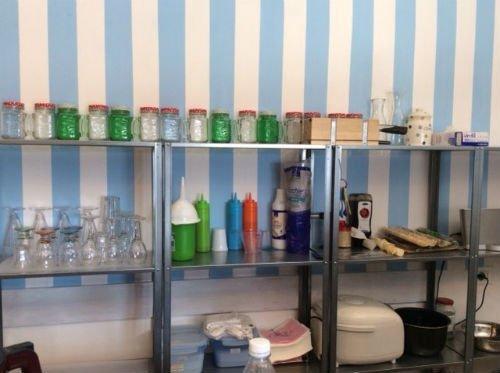 negli scaffali con dei bicchieri e altro all'interno del ristorante