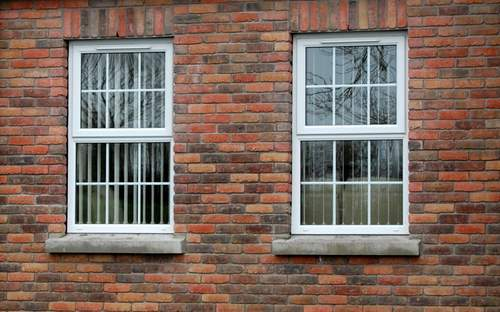 brick walling view amidst two glass windows
