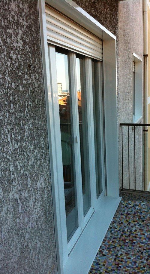 vista dall'esterno di una finestra con la tapparella leggermente abbassata