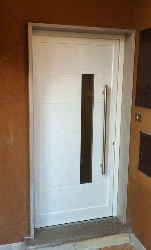 una porta bianca con un vetro verticale rettangolare e un maniglione