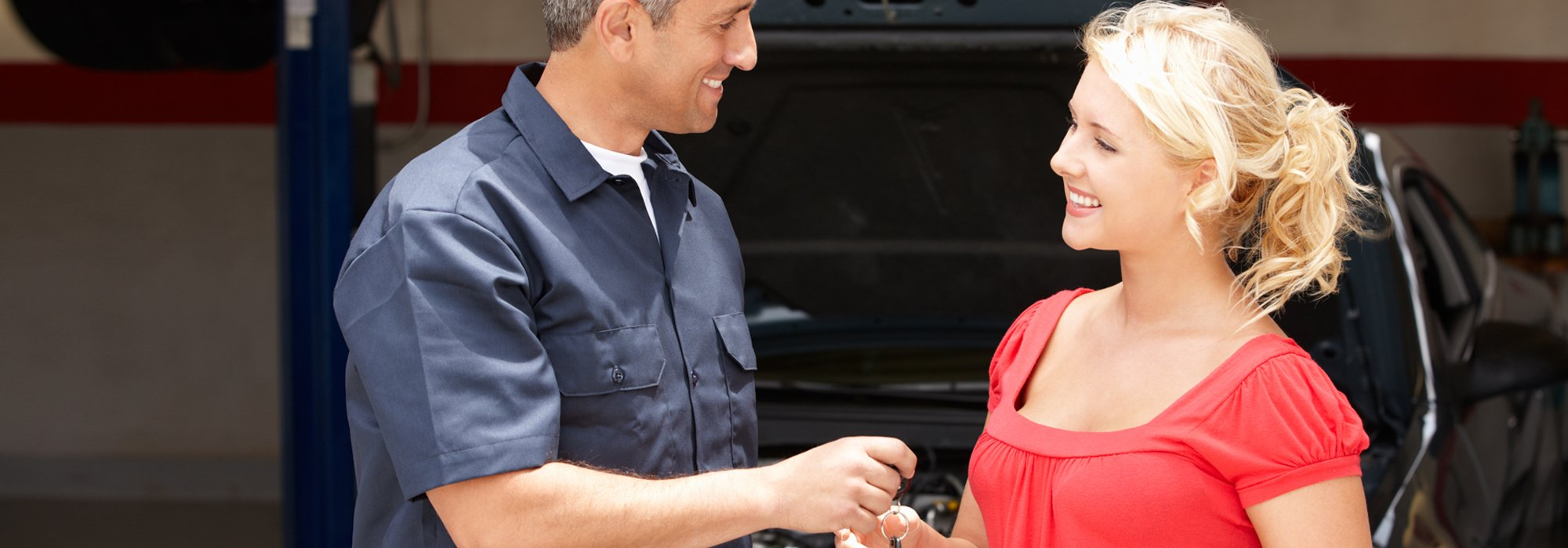 Auto mechanic handling over the keys of car to the client