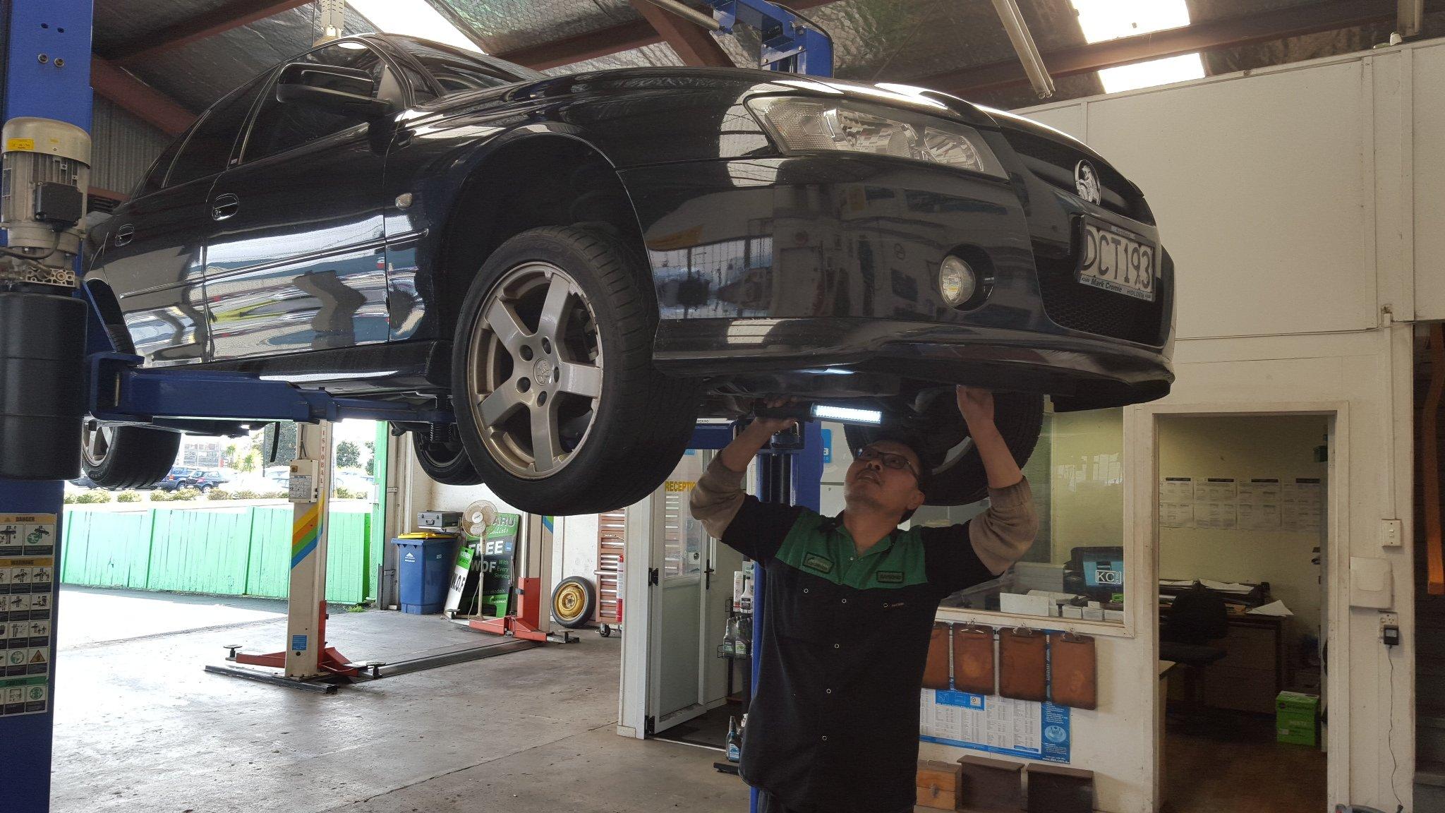 Car mechanic holding up keys after completed service
