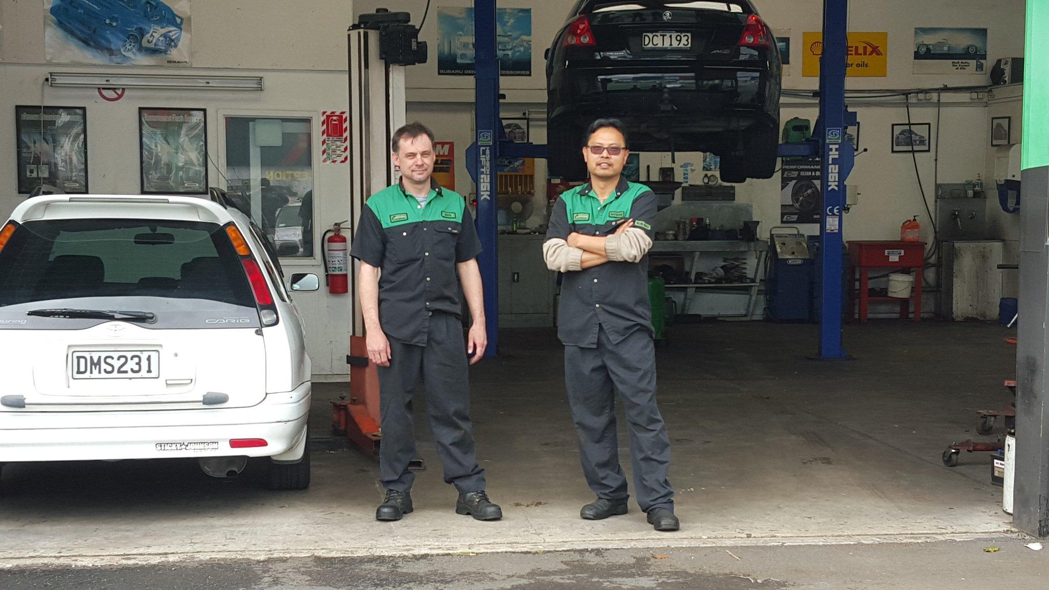 Automotive mechanics repairing car at the workshop