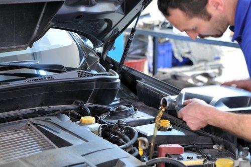 Car expert refilling oil in engine