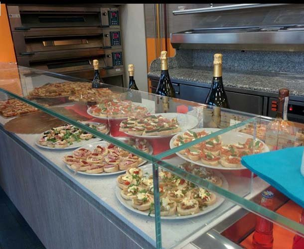 Bancone con pizze al piatto