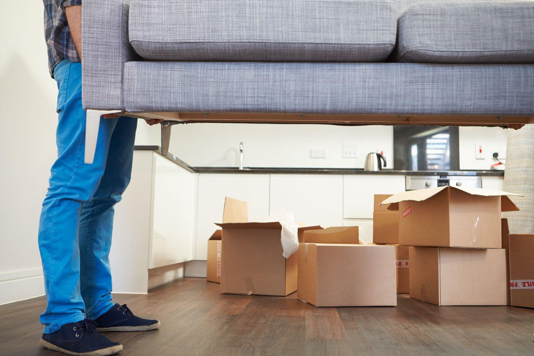 un uomo mentre solleva un divano e dietro degli scatoloni