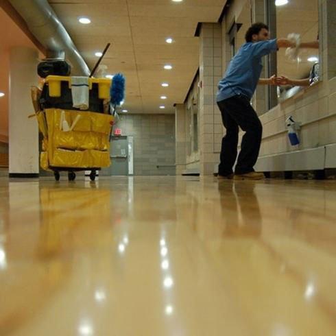 un inserviente mentre lava un vetro e si vede un carrello delle pulizie di color giallo