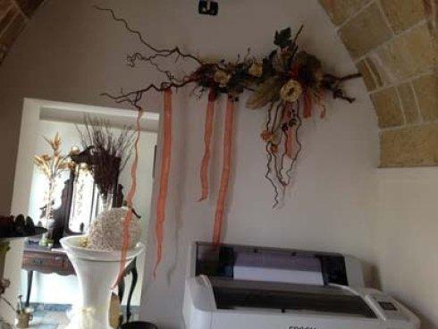 una stampante e sopra dei rami con dei fiori a muro