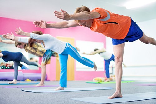People doing yoga postures for a greater flexibility and increase health