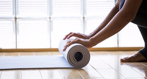 Individual rolling the mattress after the completion of the yoga session