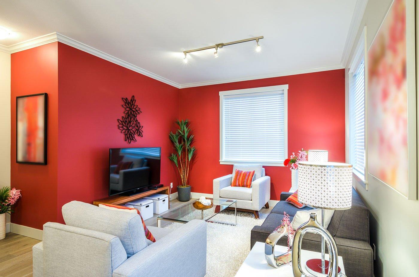 un salotto con un divano grigio,una poltrona celeste, una bianca, una tv sopra a un mobiletto e delle pareti verniciate di rosso