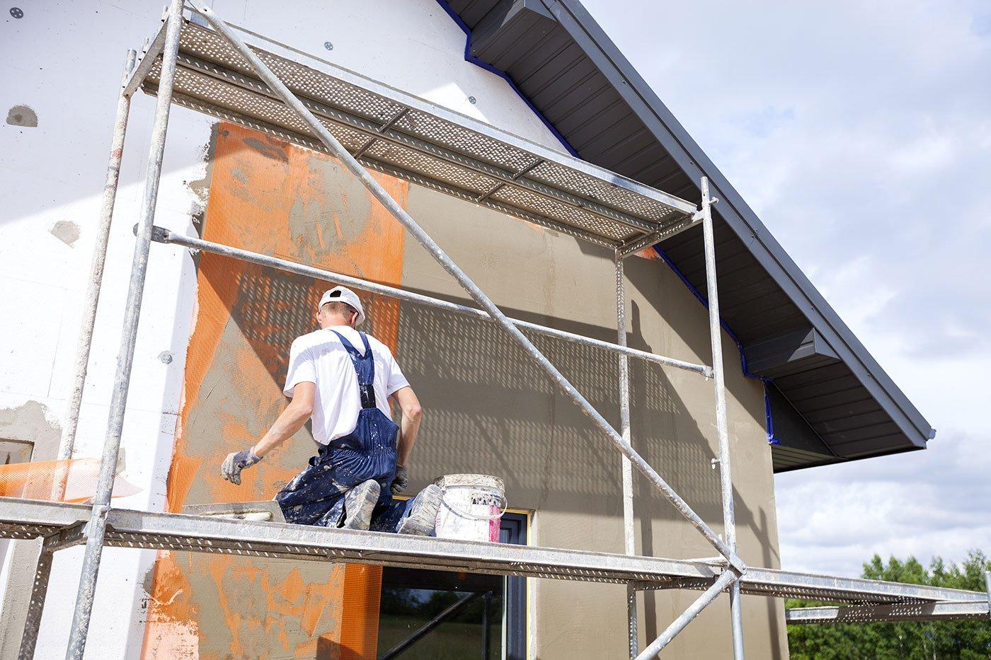 un imbianchino chinato a terra su un impalcatura in ferro di fronte a un muro arancione e grigio