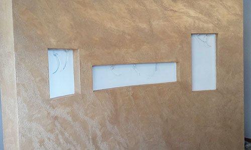 un muro color sabbia e bianco con delle rientranze