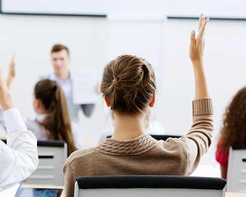 un insegnante in una classe e dei studenti che alzano le mani