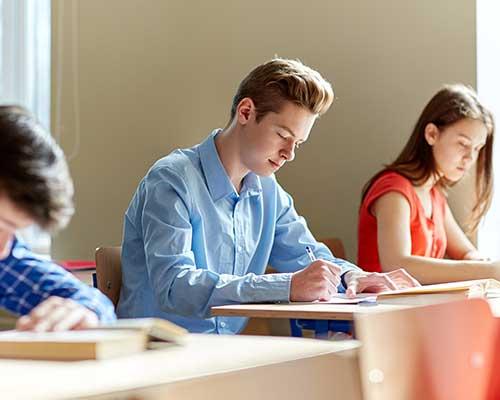 dei ragazzi seduti in una classe e mentre scrivono