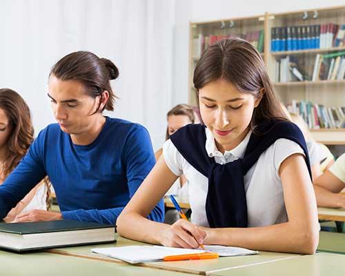 dei ragazzi in una classe mentre scrivono e vista di una libreria