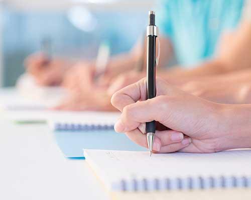 vista delle mani con le penne mentre scrivono