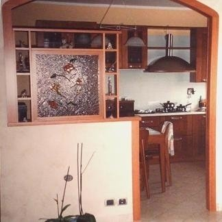 una cucina in legno con parete divisoria con struttura in legno e con vetro decorato